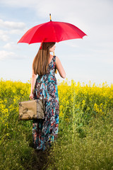 Girl with a suitcase and a red umbrella rapeseed field