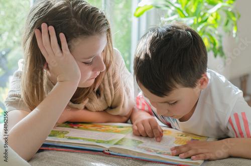 Leinwanddruck Bild Kinder lesen ein Buch