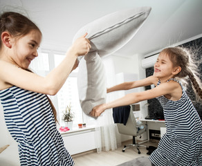 portrait of two little sisters fighting with pillows