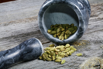 Mortar with cardamom on an old kitchen table