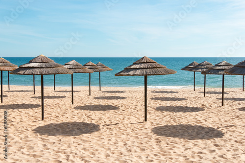 Blue sky, blue sea and parasols at beach in Portugal - 64969108