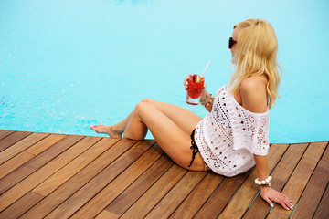 young blonde woman relaxing at the pool