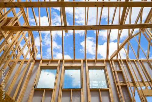New construction home framing against sky poster