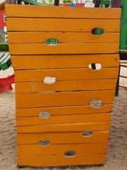 Orange wooden climbing wall ladder on kids playground