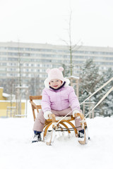 little girl sledding in snow