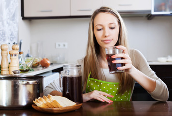 Blonde woman drinking  kvass from glass