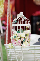 White cage with natural roses as decoration