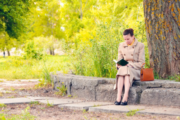 Elegant businesswoman sitting and reading an adventure book