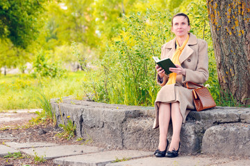 Elegant woman sitting on a wall with a book