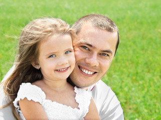 Outdoor portrait of happy smiling young man and little girl