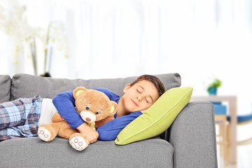 Little kid sleeping on sofa with a teddy bear at home