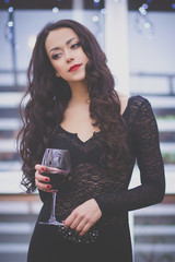 Beautiful girl with red lipstick and glass of red wine