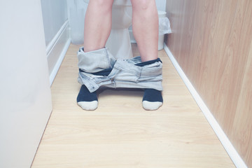 Close up on the legs of a woman on the toilet
