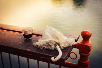 Coffee and umbrella on table by the lake