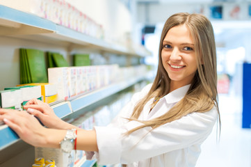 pretty pharmacist chemist woman standing in pharmacy drugstore
