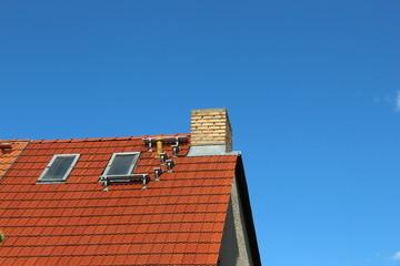 Trittstufen auf dem Spitz Dach am blauen Himmel
