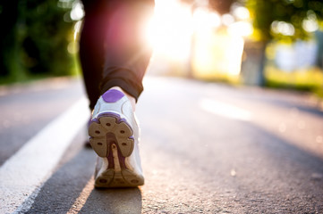Close-up of Athlete shoes while running in park. Fitness concept