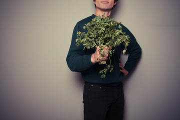 Happy young man with a big bunch of parsley