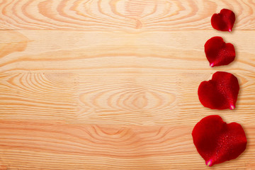 Red rose petals isolated on wood.