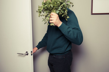 Young man with parsley is answering the door