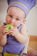 Little boy in a chief hat sitting on a floor eating apple