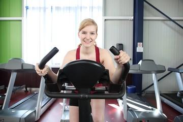 Frau im Fitnessstudio trainiert auf Fahrrad