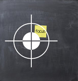 Focus text concept on a sticky note glued on a blackboard poster