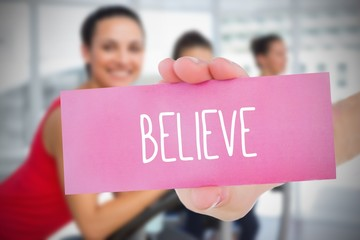 Woman holding pink card saying believe