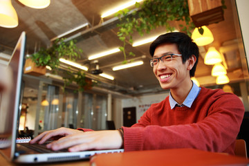 Cheerful asian man in glasses typing on laptop in office