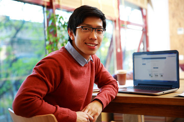 Young asian man sitting at the table with laptop