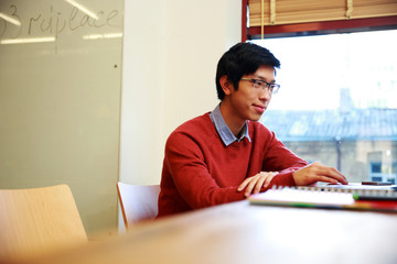 Young asian student in glasses sitting at the table