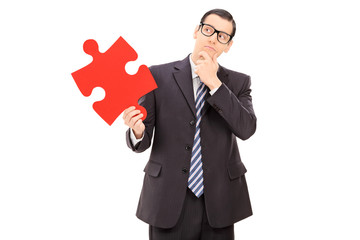 Pensive businessman holding a piece of puzzle