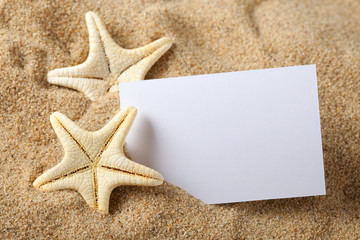 Starfish and blank paper sheet on beach