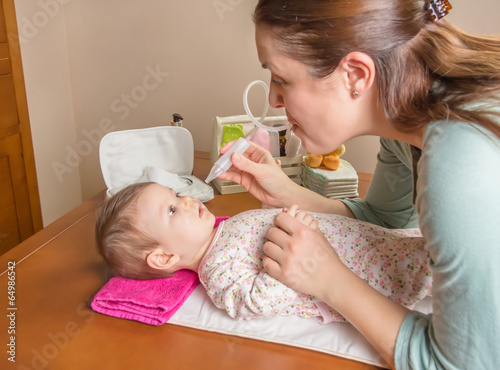Mother cleaning mucus of baby with nasal aspirator - 64986542