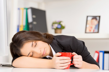 young brunette sleeping at working time.