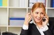 Auszubildende telefoniert mit Smartphone im Büro