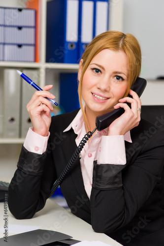 canvas print picture Auszubildende telefoniert im Büro.