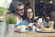 Embracing couple using mobile phone in cafe - 64991568