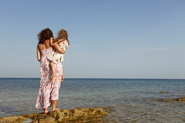 Back view of mother and  daughter looking on the sea