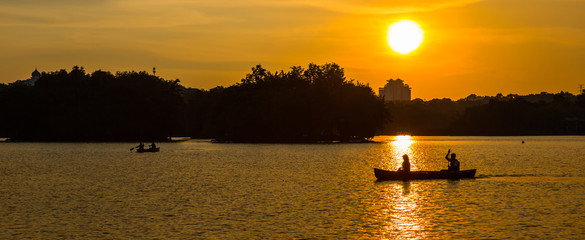 Silhouette of a couple canoeing in a lake, Malaysia
