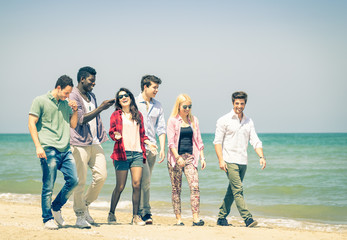 Group of happy friends walking a talking at the beach - Concept