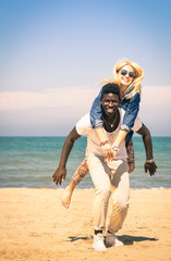 Young couple playing at the beach - Fun with piggyback jump