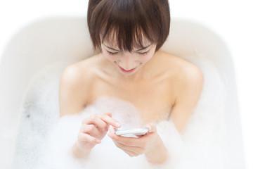 お風呂でスマートフォンを使う女性