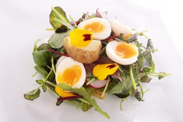 quail egg with potato and watercress flower salad