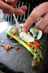chef preparing poached quail eggs on asparagus