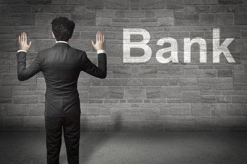 businessman standing in front of a wall hands up bank