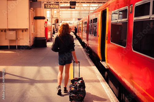 Young woman about to board a train - 64999128