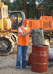 worker in helmet holding a canister of fuel