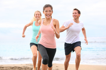 Friends running on beach jogging