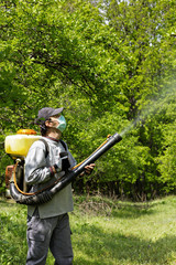 Young farmer spraying the trees with chemicals
